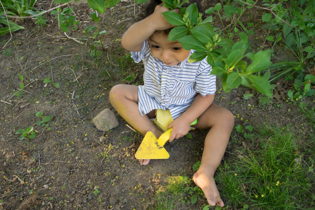 Small child hiding in a bush and sitting in the dirt with a yellow shovel in his hand.