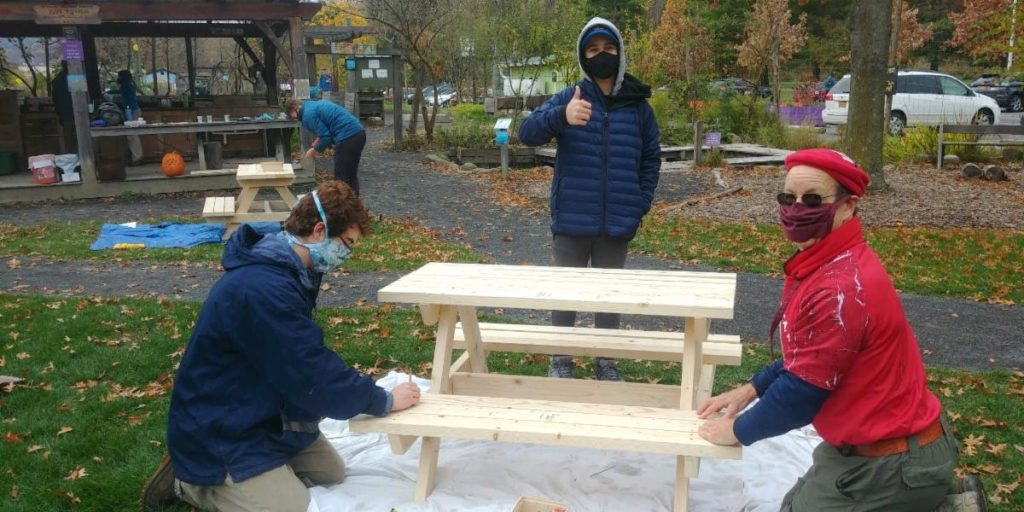 Three folks sanding a natural wood picnic table, one is giving a thumbs up.