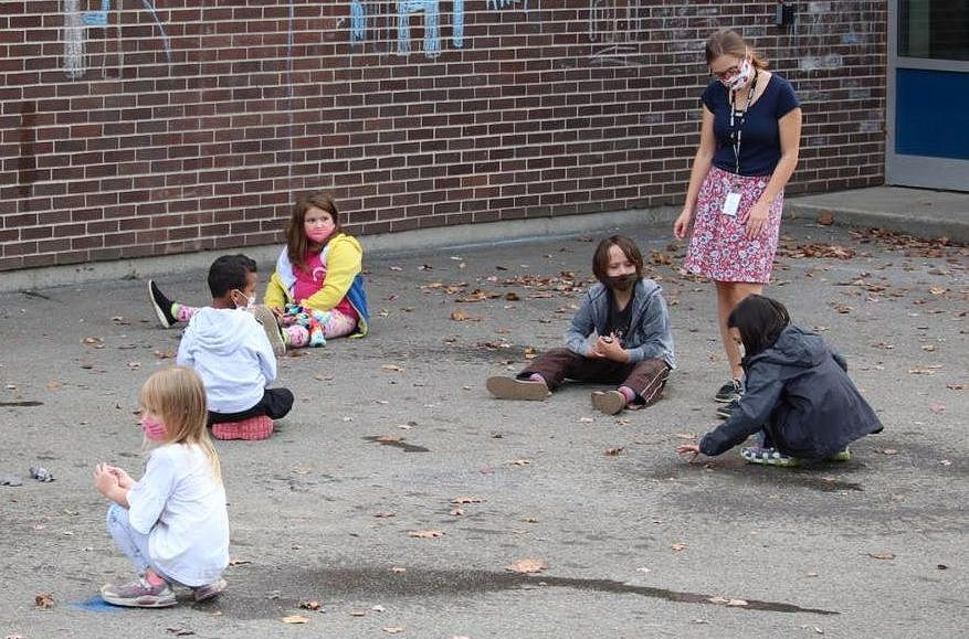 Several seated children on pavement, a teacher stands among them.