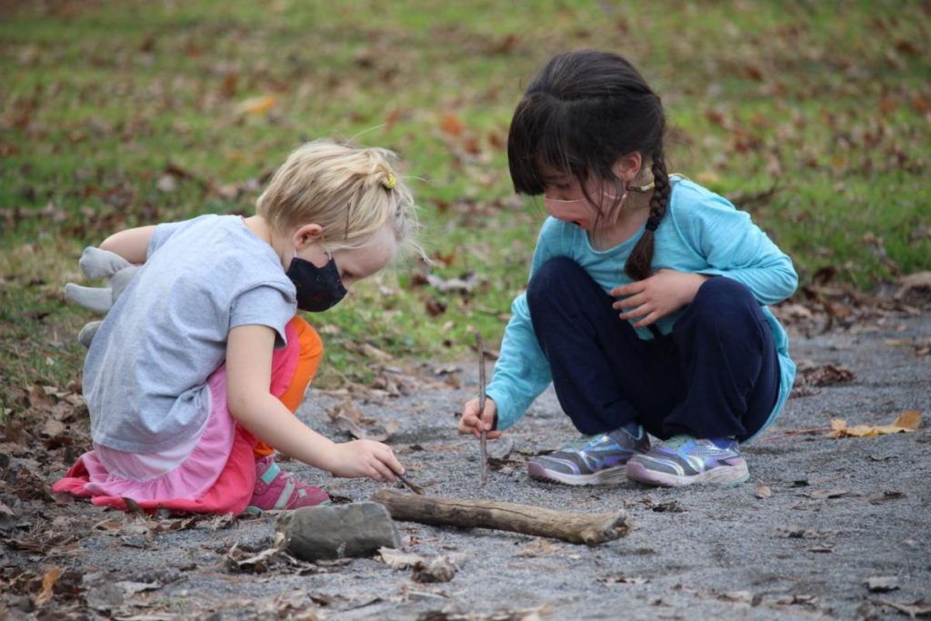 Two younger children, wearing face mask coverings, playing in the dirt with twigs.