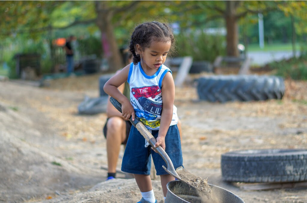 Small child shovels dirt into a bucket.