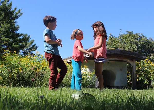 Three small children play in front of the troll house.