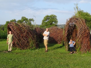 Three boys play in the willow sculpture.
