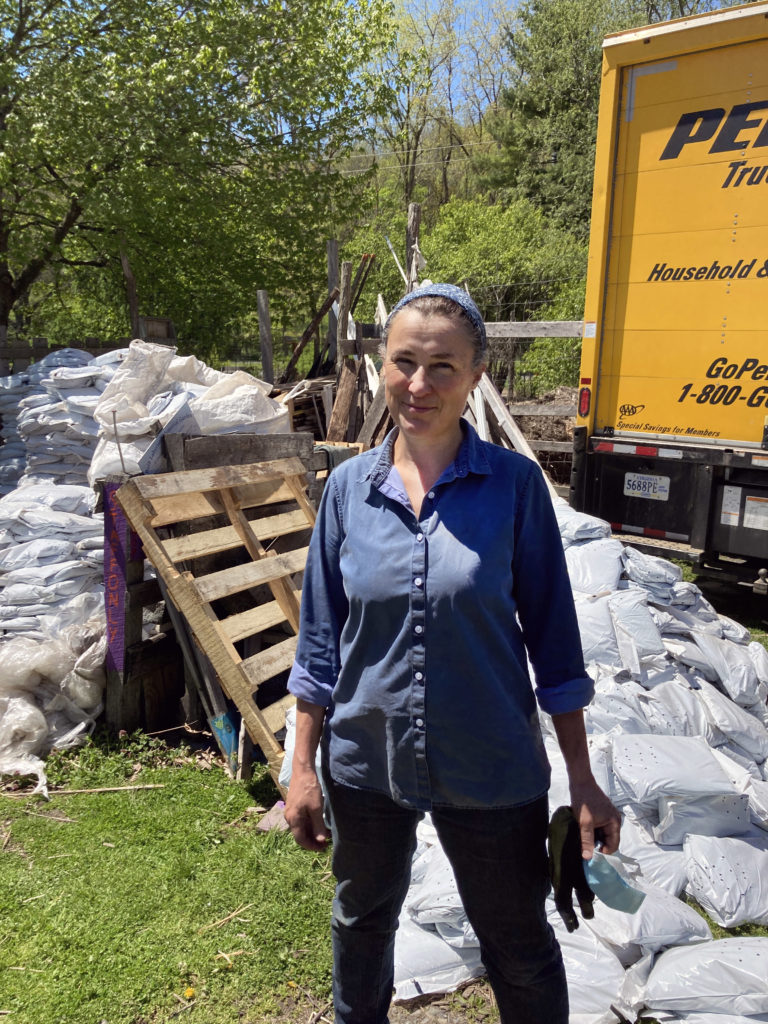 Peggy Arcadi stands in front of a large yellow truck, piles of large white bags full of soil behind them. They are smiling at the camera.