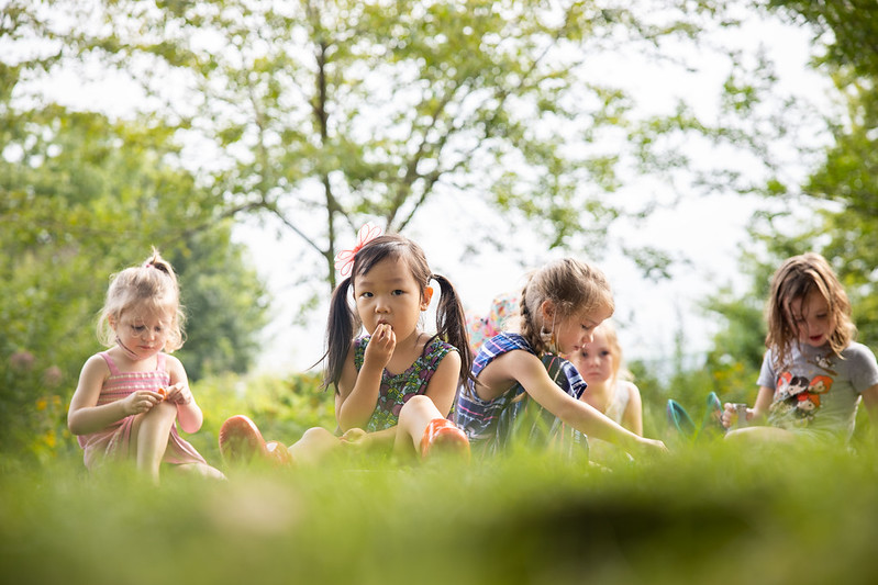 Several young children sit in the grass together.